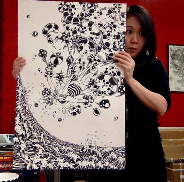 Yuko Shimizu holding her artwork