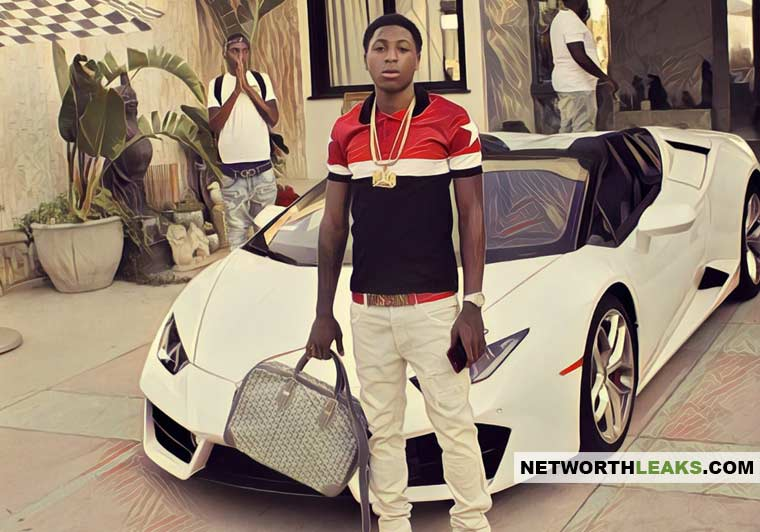 NBA YoungBoy standing next to his Lamborghini